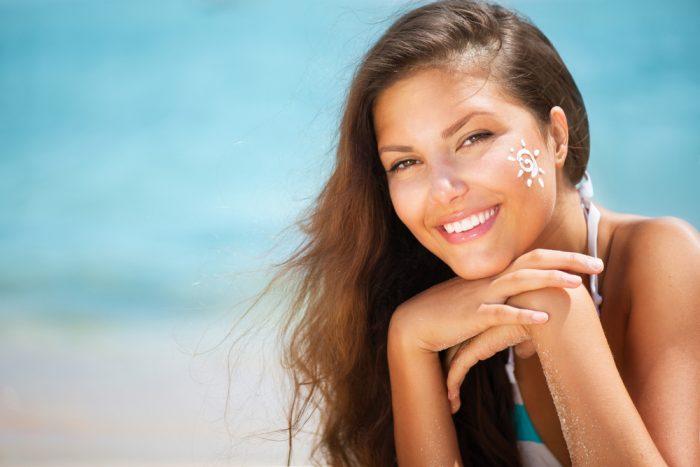 Девушка улыбается на фоне моря с нарисованным солнцем на щеке