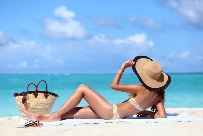 Девушка сумкой и в шляпке лежит на берегу моря