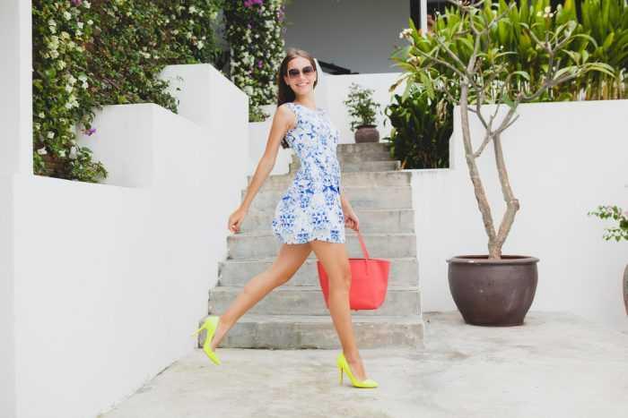Счастливая девушка в коротком платье с коралловой сумкой и в желтых туфлях