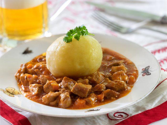 Гуляш в тарелке с вареным картофелем