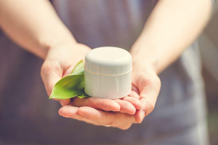 Крем для лица с зеленым листиком в руках