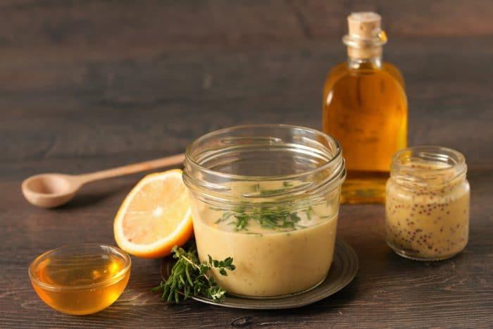 Мед, горчица и пол лимона на дернвянной поверхности