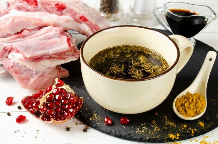 Соус,приправа и гранат возле мяса