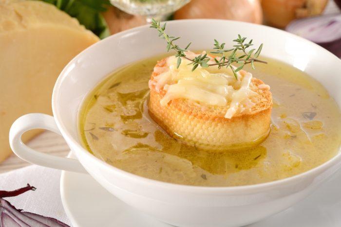 Суп в белой тарелке с гренкой