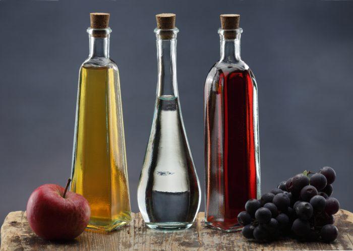 Три бутылки с яблочным уксусом настолевозле винограда и яблока