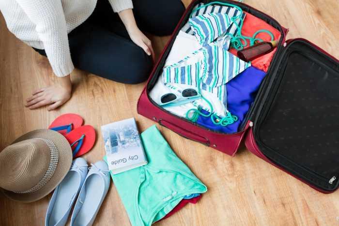 Упакованный чемодан и вещи на полу