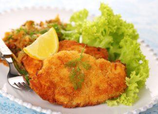 Венский шницель на тарелке с зеленью и лимоном
