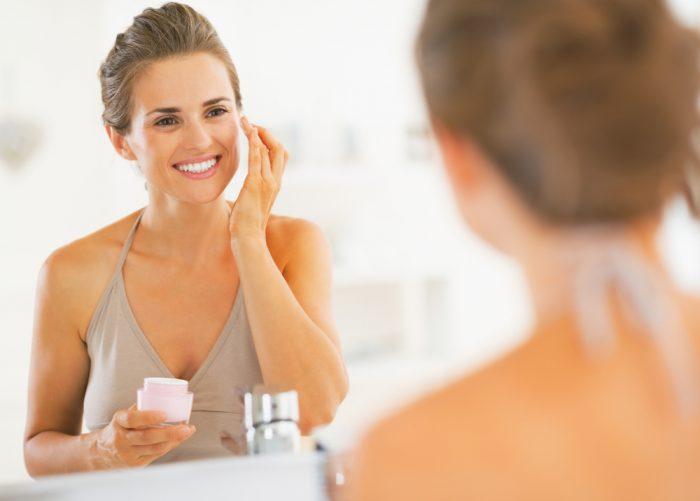 Девушка наносит крем на лицо и улыбается перед зеркалом
