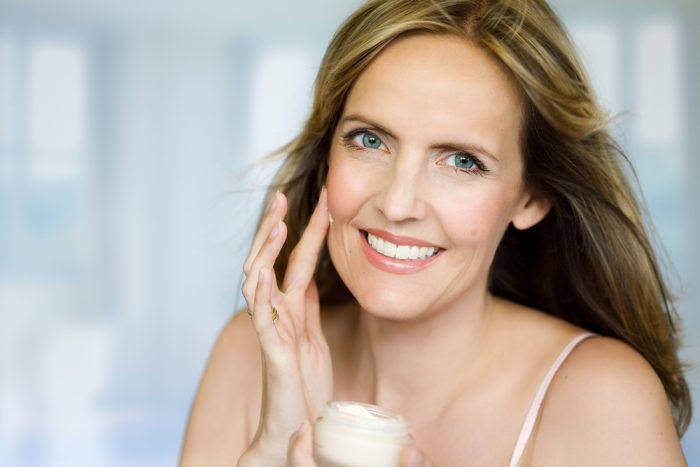 Женщина улыбается и наносит крем налио
