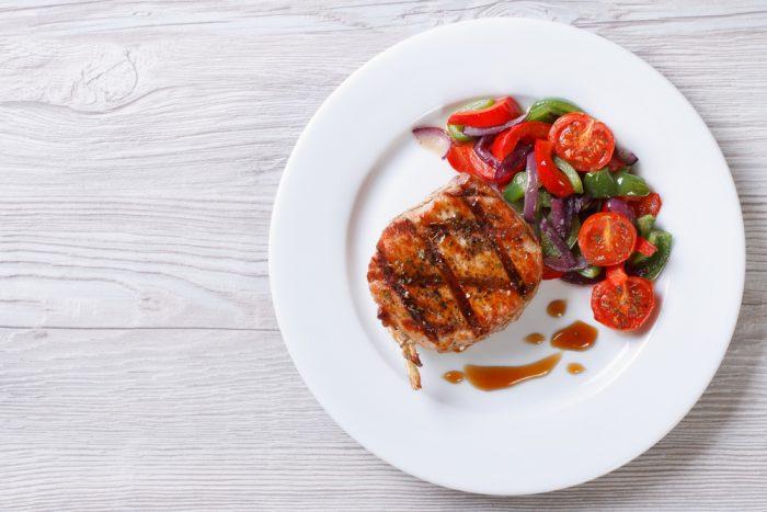 биток с соусом и овощами на белой тарелке