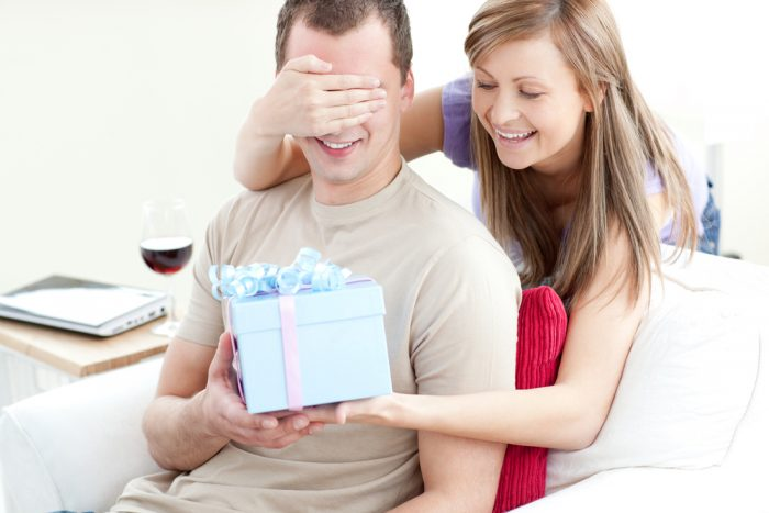Девушка дарит мужчине подарок