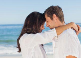 Девушка на пляже положила руки на плечи мужчине