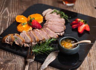 Порезанная утиная грудка на тарелке с соусом, клубникой и апельсином