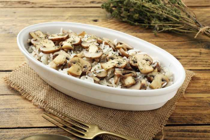 Рис с грибами в белой глубокой тарелке