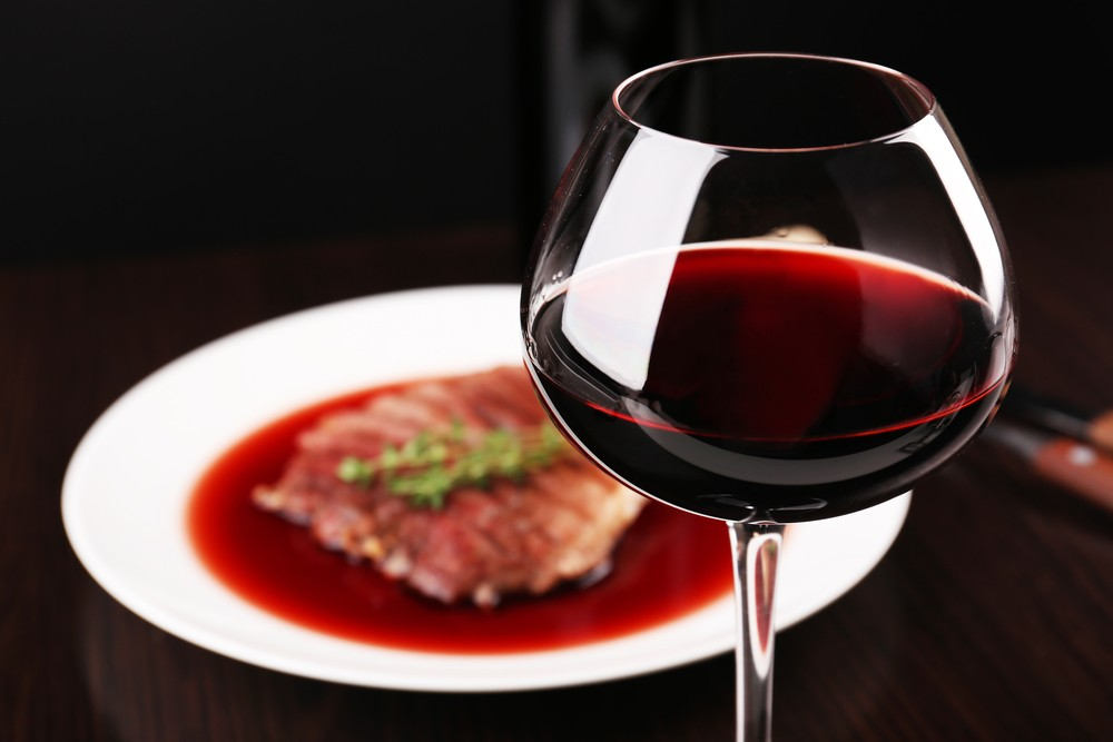 тарелка с мясом и бокал с красным вином