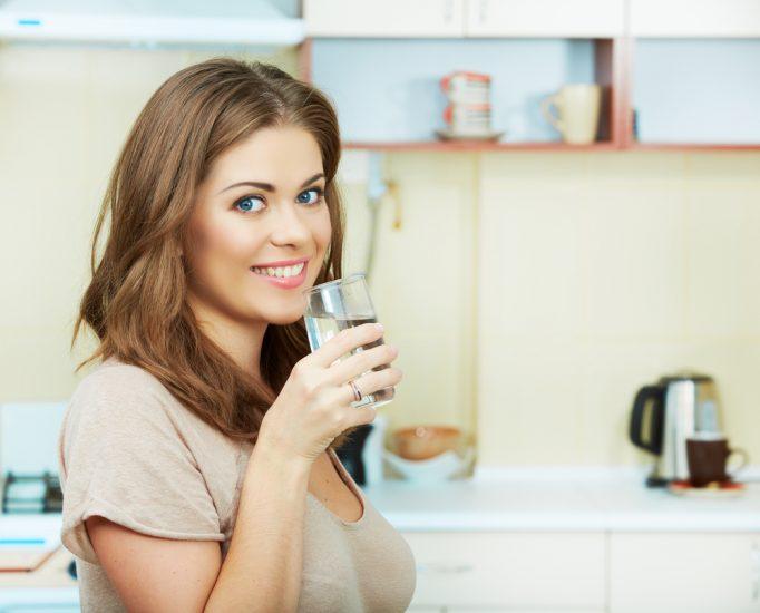 Девушка на кухне пьет воду