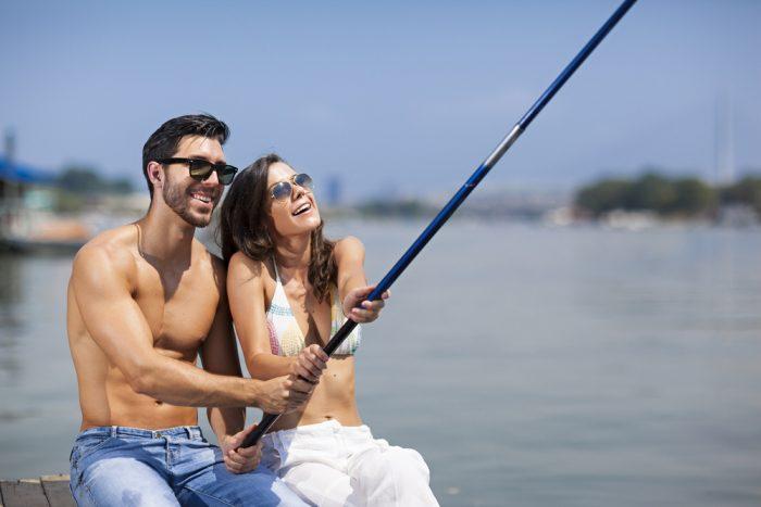 Парень с девушкой на рыбалке держат удочку