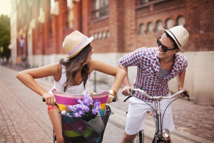 Девушка с парнем едут на перегонки на велосипедах