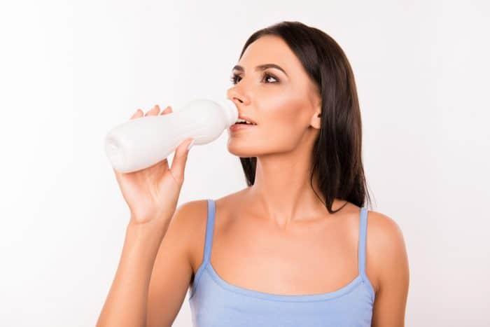 Девушка в серой майке пьет йогурт