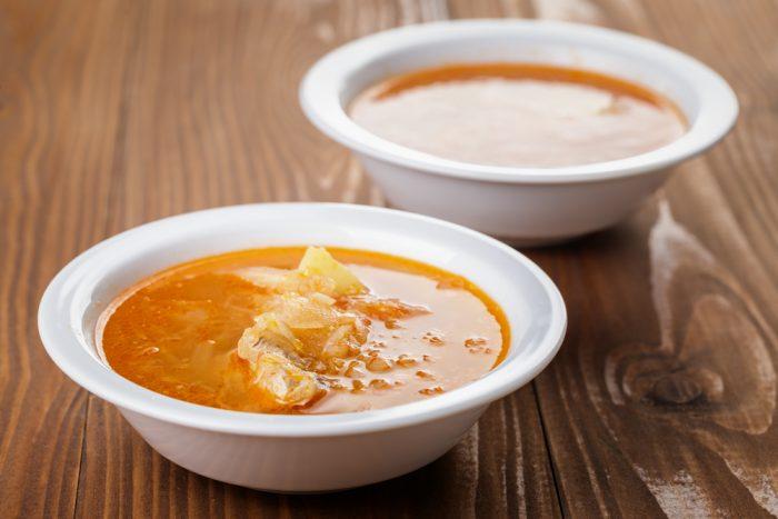 Две белые тарелки с супом