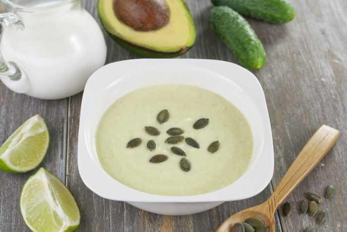 Крем -суп с тыквенными семечками в тарелке возле лайма и авокадо