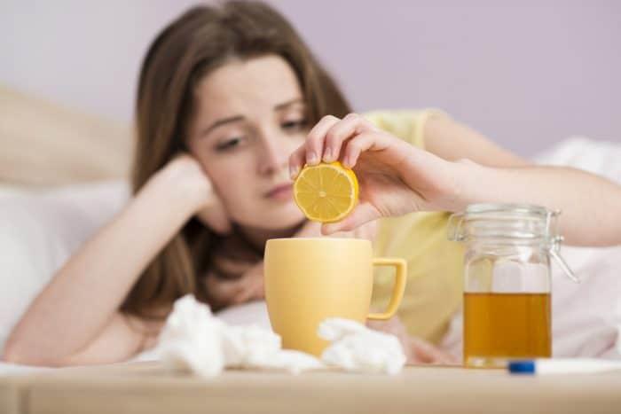 Простуженная девушка держит лимон на чаем