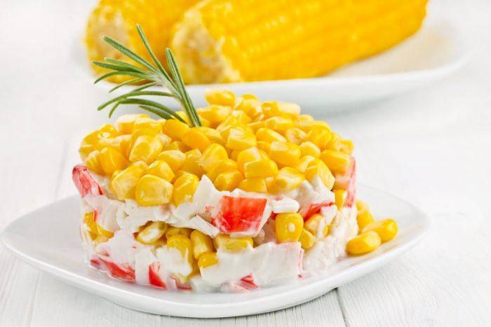 Салат крабовый с кукурузой на белой тарелке