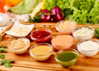 Цветные соусы в стеклянных тарелках на деревянном подносе