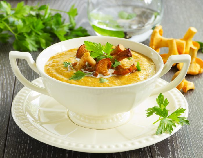 Суп с грибами, с петрушкой на белой тарелке с ручками, на блюдце