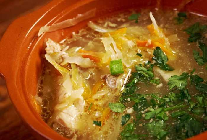 Суп из квашенной капусты с зеленью в тарелке