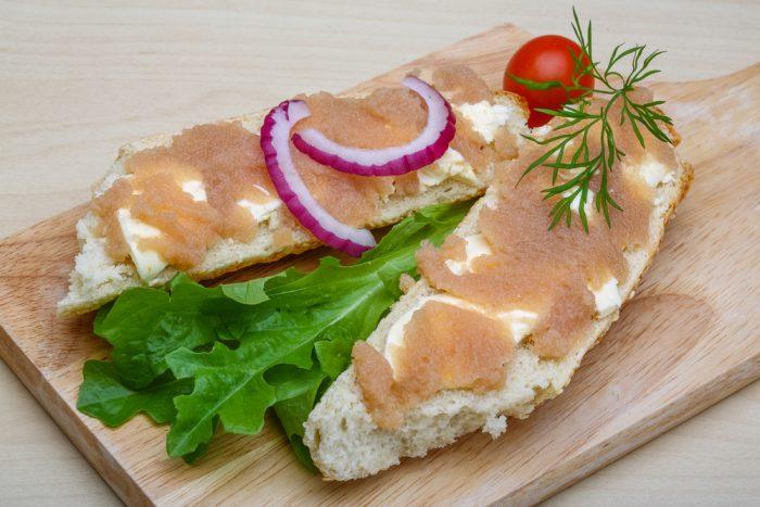 Хлеб с икрой трески на досточке с луком и помидором