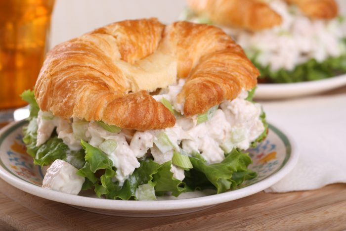 Круасан с курицей и салатом на тарелке