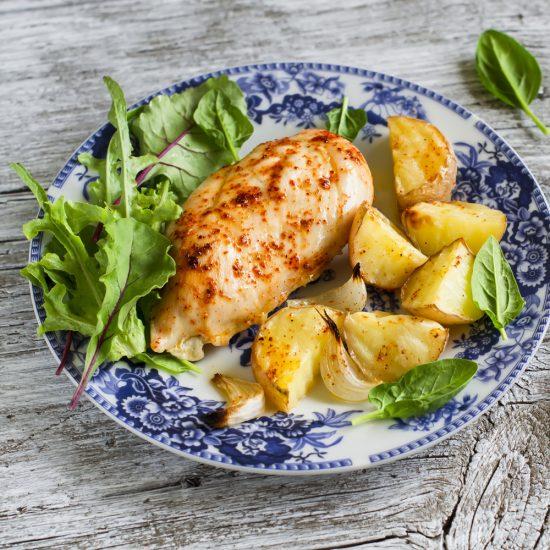 Куриная грудка с картофелем и салатом на тарелке