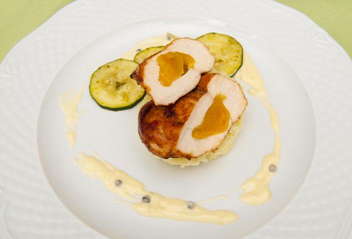 Куриное филе с персиком и соусом на тарелке
