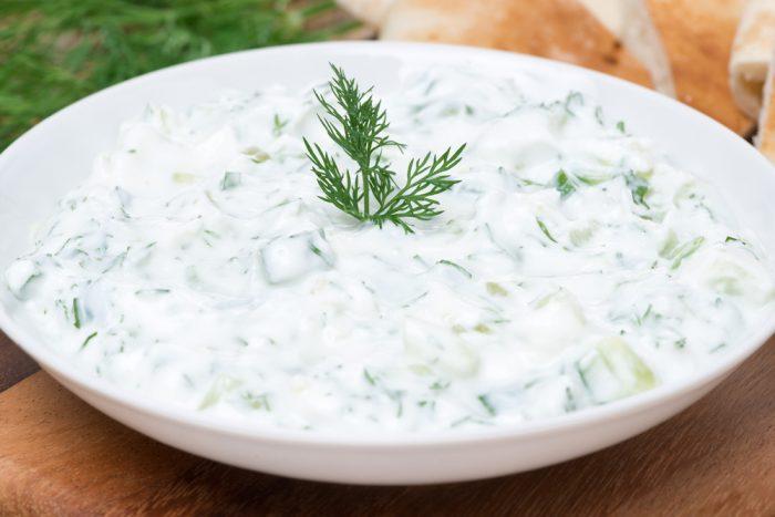 Огурец с йогуртом в белой тарелке