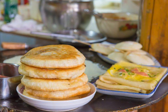 Пышные оладьи на тарелке возле тостов