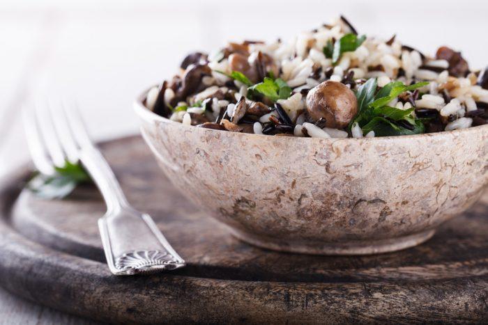 Рис с грибами и зеленью в тарелке на подставке с вилкой