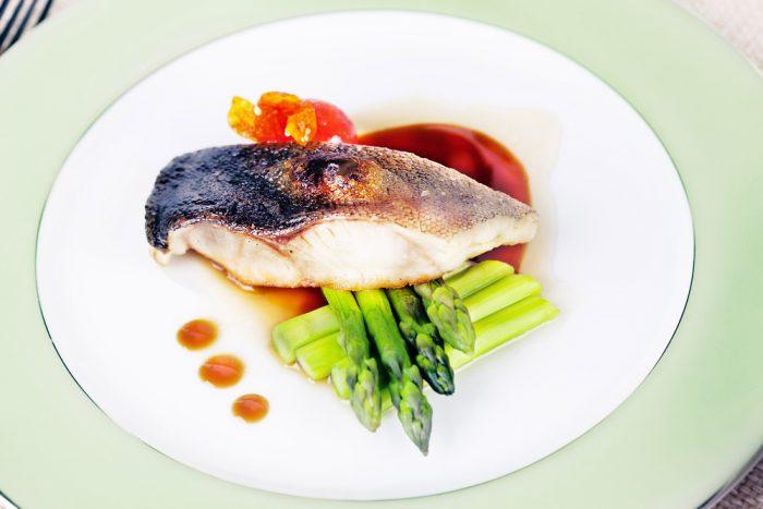 Рыба с спаржей и соусом на тарелке