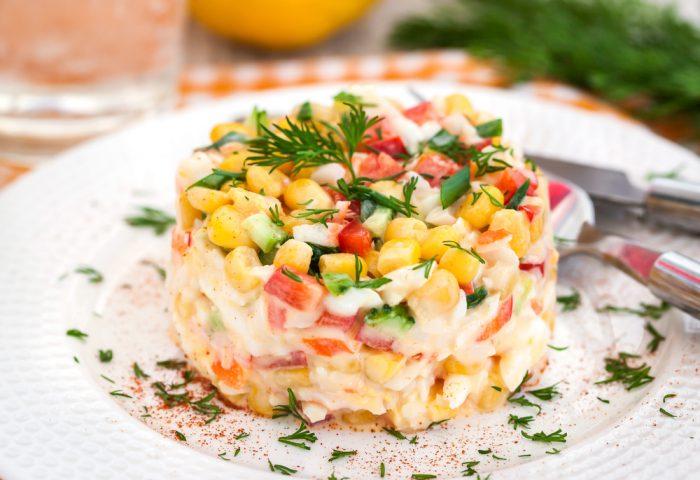 Салат с крабов и кукурузы на тарелке с зеленью