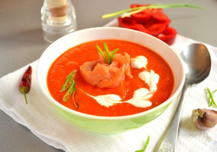 Суп в тарелке возле чеснока и перца