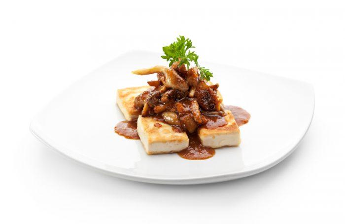 Tofu mit Pilzen auf einem weißen Teller