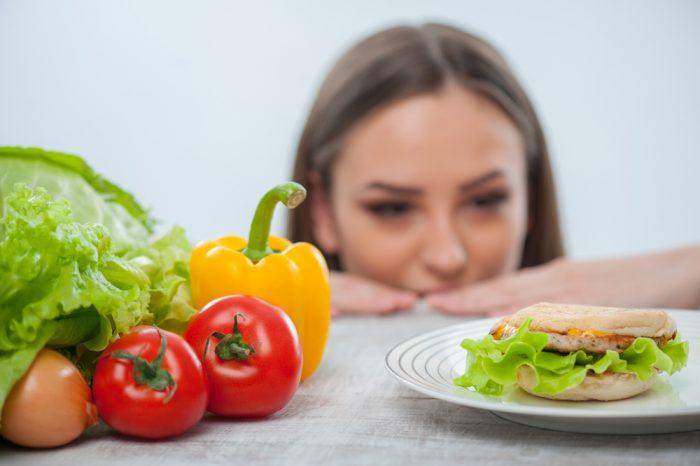 Девушка смотрит на гамбургер с аппетитом
