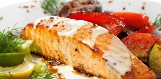 красная рыба на тарелке с овощами, лимоном и зеленью