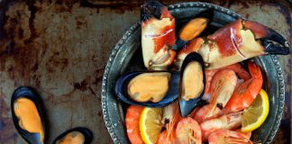 Морепродукты та черной тарелке на сером фоне