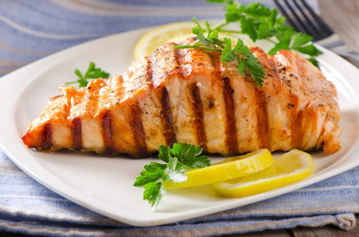 На тарелке с лимоном жареный лосось на гриле