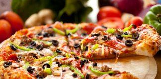 Пицца с оливками и зеленым перцем на деревянной подставке