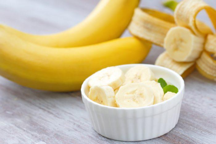 Порезанные бананы в тарелке возле целых