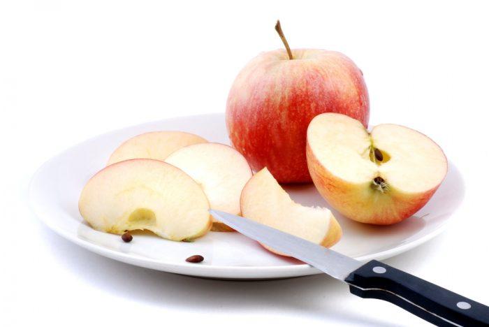 Разрезаное яблоко на белой тарелке