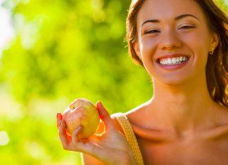 Счастливая девушка держит яблоко