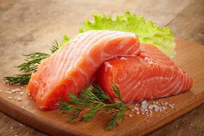 Сырой лосось на досточке с солью и укропом